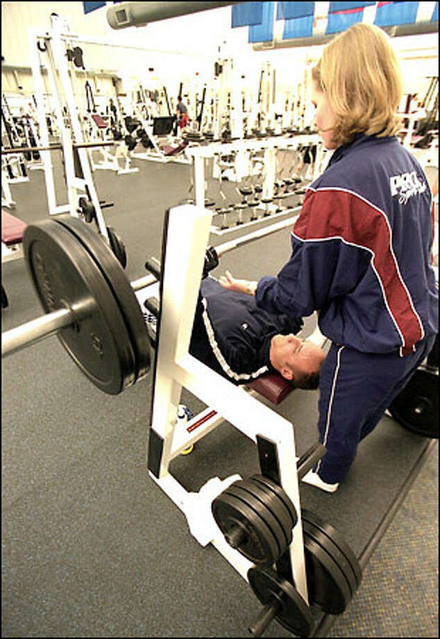 David Ursino lifts weights at the Pro Sports Club in Bellevue, with Sonja Brandstrom serving as his spotter. Photo: Phil H. Webber/Seattle Post-Intelligencer