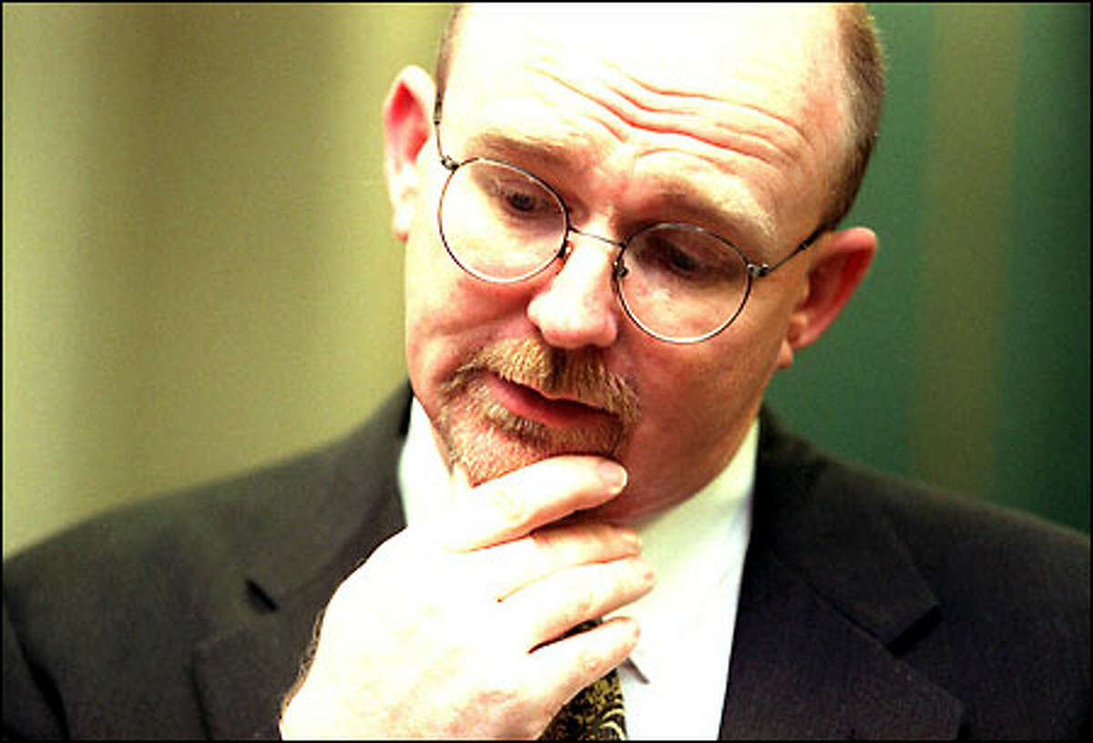 Dr. Barry Logan, head of the state crime lab, ponders a question during a news conference to announce that the federal government is giving $500,000 to King County to help pay for DNA testing of the victims.