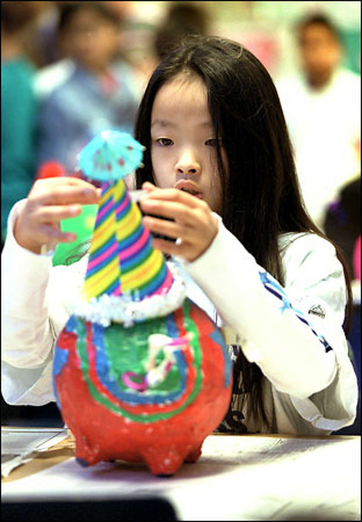 Third-grader Chunvanny Lim works on her pig, Rainbow Star, as part of Sanislo Elementary's Pigs on parade project.