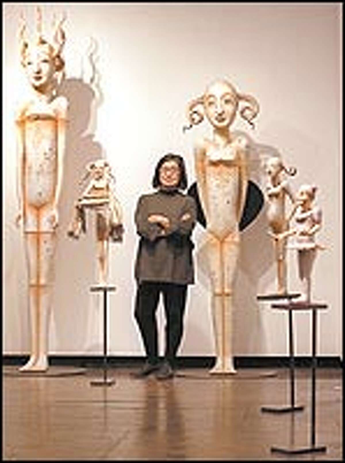 Time hasn't doused her creative fire: Patti Warashina poses with some of her lusty creations at the Howard House, her first solo show in 10 years.