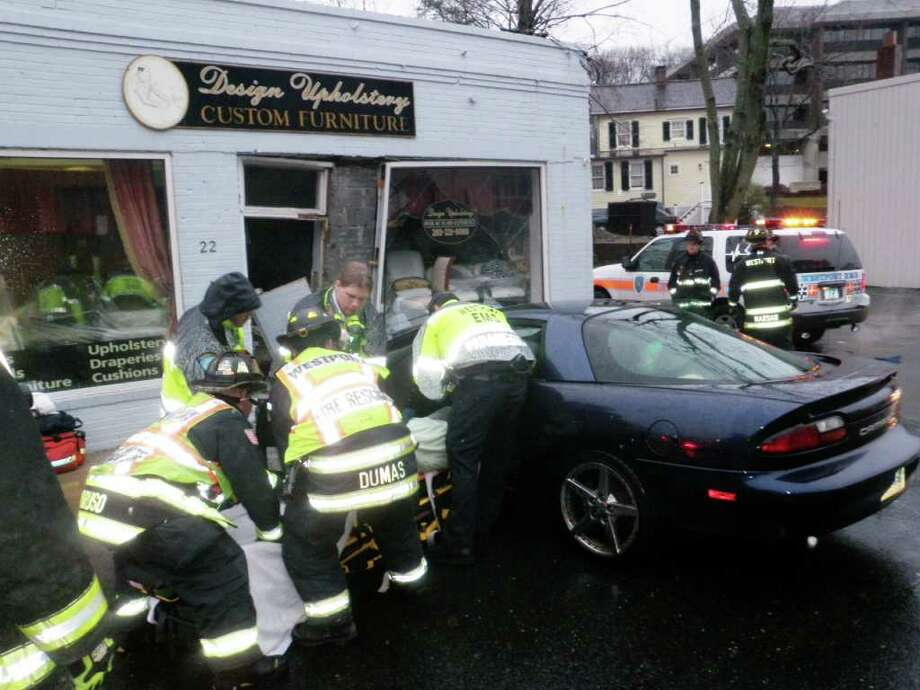 Firefighters and EMS personnel attend to a woman who crashed her Chevy Camaro into a storefront shortly before 7 a.m. on March 11. The driver claimed her gas pedal got stuck. Photo: Contributed Photo / Westport News