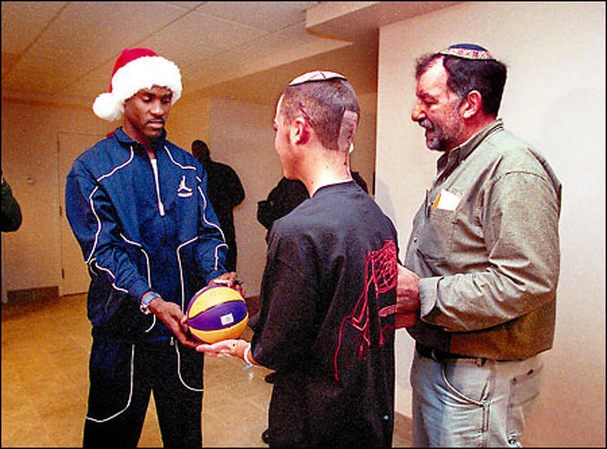 Sonics star Gary Payton autographs a basketball for Children's Hospital patient Ari Grashin, recovering from brain tumor surgery, as his father David Grashin looks on.