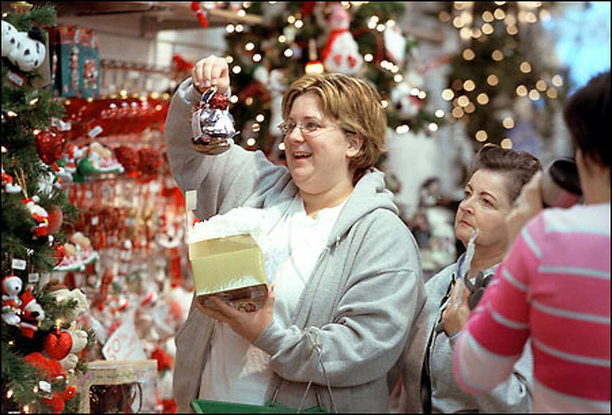 """Alesia Pearson went from Tacoma to take advantage of the after-Christmas sales at the SuperMall in Auburn, here she holds up a """"Polonaise Collection"""" figure of Raggedy Ann and Andy at the Christmas Corner store. With everything 50 percent off, the ornament, which usually is priced at $45, cost her $22.50. Similar bargains could be found all over the Seattle area yesterday."""