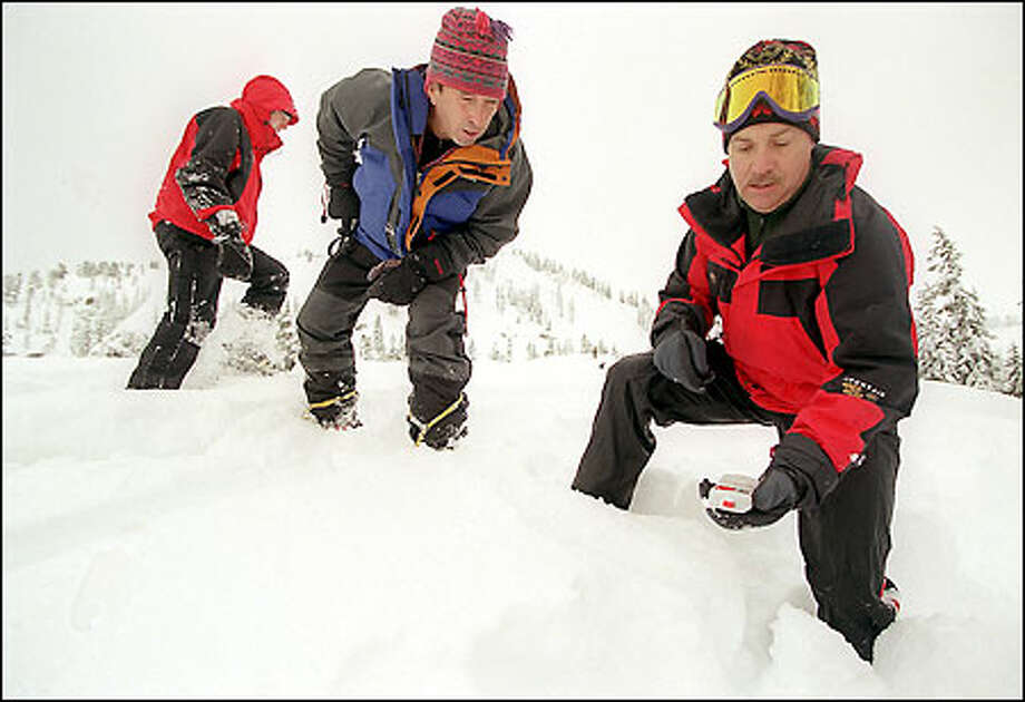 Avalanche safety expert Gary Brill, center, looks at the reading on KING-5 weather expert Jeff Renner's transceiver during a class on how to find an avalanche victim. Photo: Meryl Schenker/Seattle Post-Intelligencer