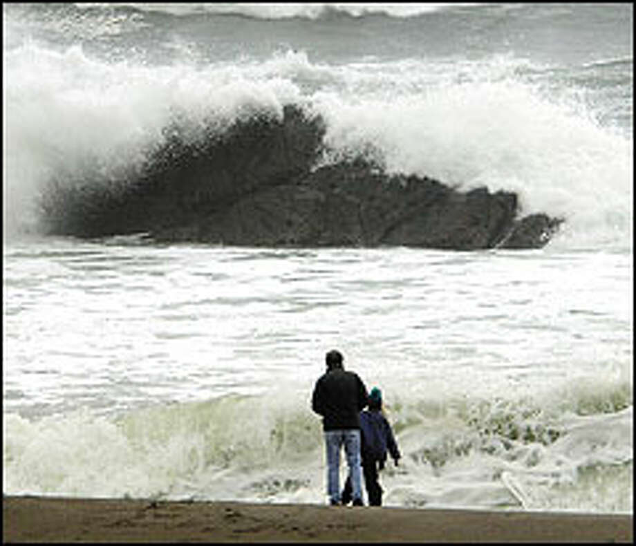 Beachcombers watch as storm-tossed waves crash over rocks near Depoe Bay, Ore. Long a favorite activity of local residents, storm watching has become a tourist draw over the past few years. Photo: THE ASSOCIATED PRESS