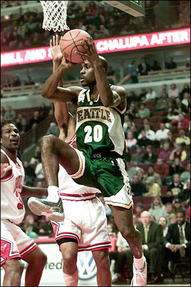 Gary Payton drives around Chicago Bulls guard Kevin Ollie as forward Charles Oakley, left, looks on. Payton had 26 points and five assists. Photo: / Associated Press