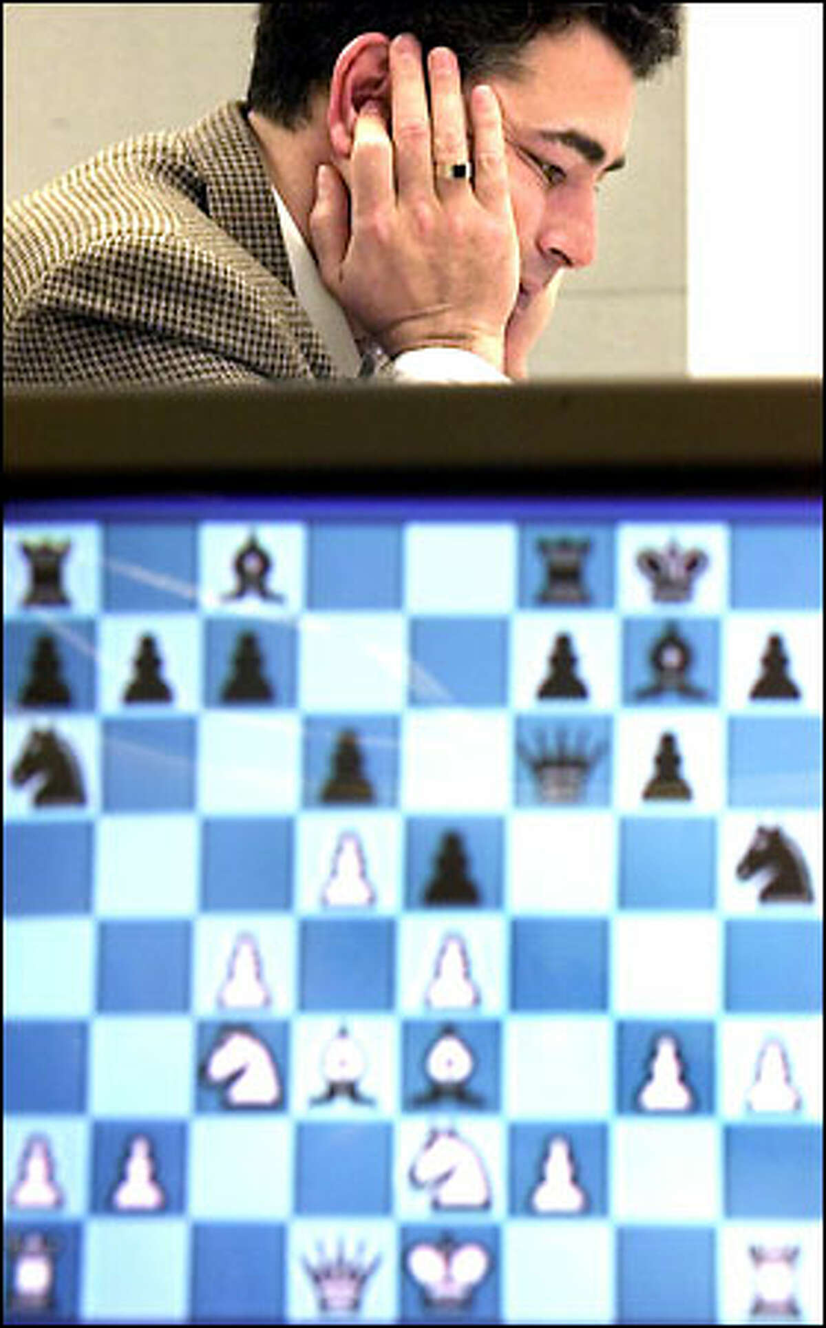 Yasser Seirawan plays in the U.S. Chess Championships. In front is a screen that displays the progress of the game.