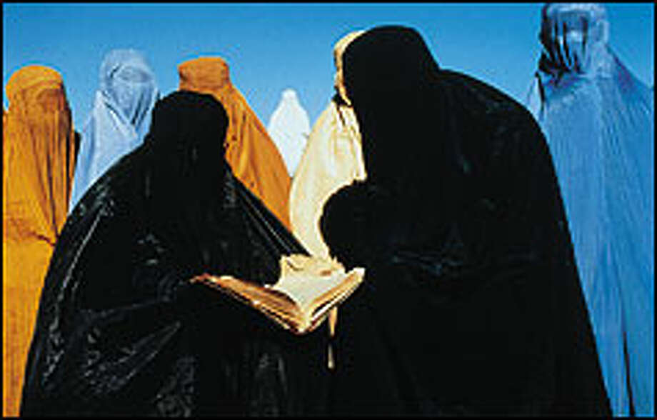 """Covered in identity-masking burqas, Afghan women gather in a scene from """"Kandahar."""""""