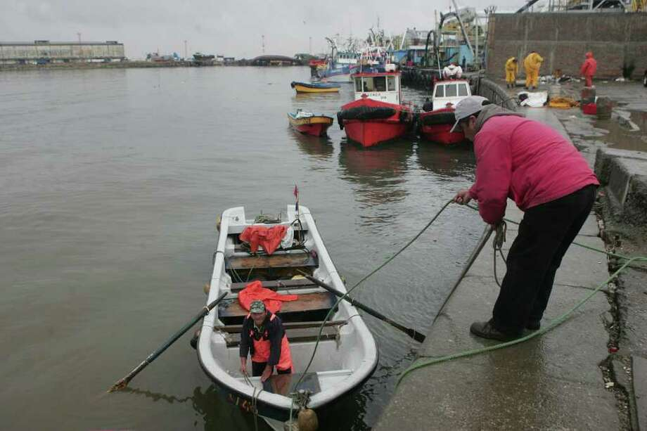"Fishermen prepare their boat in the port of Talcahuano, 500 km south of Santiago, as a preventine measure after Chilean President Sebastian Pinera issued a ""preventive alert"" due to the imminent threat of a tsunami following a powerful earthquake off Japan, though telling citizens to remain calm and continue normal life. Reactions to the possible arrival of a giant wave varied in Latin American nation along the Pacific coast, most of which have experienced devastating earthquakes in the past.  AFP PHOTO/CLAUDIO POZO (Photo credit should read CLAUDIO POZO/AFP/Getty Images) Photo: CLAUDIO POZO"