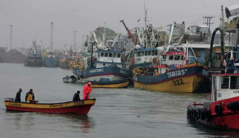 """Fishermen prepare their boat in the port of Talcahuano, 500 km south of Santiago, as a preventine measure after Chilean President Sebastian Pinera issued a """"preventive alert"""" due to the imminent threat of a tsunami following a powerful earthquake off Japan, though telling citizens to remain calm and continue normal life. Reactions to the possible arrival of a giant wave varied in Latin American nation along the Pacific coast, most of which have experienced devastating earthquakes in the past.  AFP PHOTO/CLAUDIO POZO (Photo credit should read CLAUDIO POZO/AFP/Getty Images) Photo: CLAUDIO POZO"""