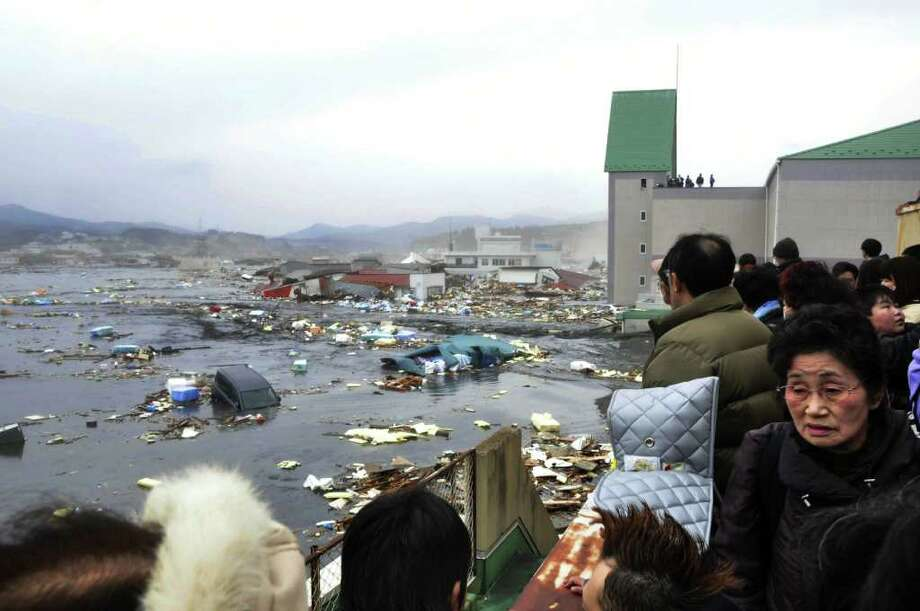 Local residents watch the devastation provoked by a tsunami tidal wave smashing vehicles and houses at Kesennuma city in Miyagi prefecture, northern Japan on March 11, 2011. A massive 8.9-magnitude earthquake shook Japan, unleashing a powerful tsunami that sent ships crashing into the shore and carried cars through the streets of coastal towns. AFP PHOTO / YOMIURI SHIMBUN   (JAPAN OUT, RESTRICTED TO EDITORIAL USE) (Photo credit should read STR/AFP/Getty Images) Photo: STR