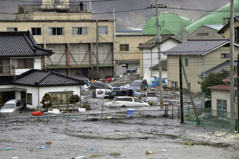 A tsunami, tidal wave smashes vehicles and houses at Kesennuma city in Miyagi prefecture, northern Japan on March 11, 2011. A massive 8.9-magnitude earthquake shook Japan, unleashing a powerful tsunami that sent ships crashing into the shore and carried cars through the streets of coastal towns. AFP PHOTO / YOMIURI SHIMBUN   (JAPAN OUT, RESTRICTED TO EDITORIAL USE) (Photo credit should read STR/AFP/Getty Images) Photo: STR