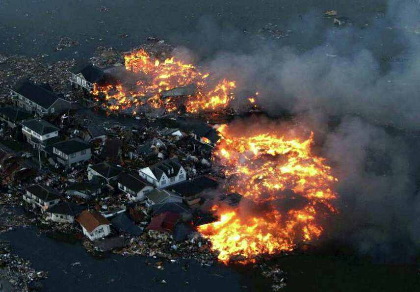 This aerial shot shows houses in flame after being hit by a tsunami at Natori city in Miyagi prefect