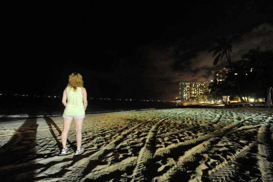 HONOLULU, HAWAII - MARCH 11: A woman watcheds as waves hit the deserted Waikiki shoreline on March 1