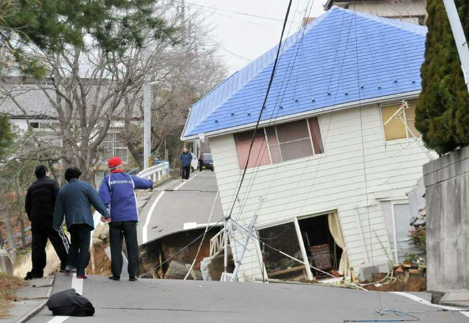 residents check the damaged done on a road a house in Sukagawa city, Fukushima prefecture, in northern Japan on March 11, 2011.  A massive 8.9-magnitude earthquake shook Japan, unleashing a powerful tsunami that sent ships crashing into the shore and carried cars through the streets of coastal towns.     AFP PHOTO / FUKUSHIMA MINPO via JIJI PRESS (Photo credit should read FUKUSHIMA MINPO/AFP/Getty Images) Photo: FUKUSHIMA MINPO