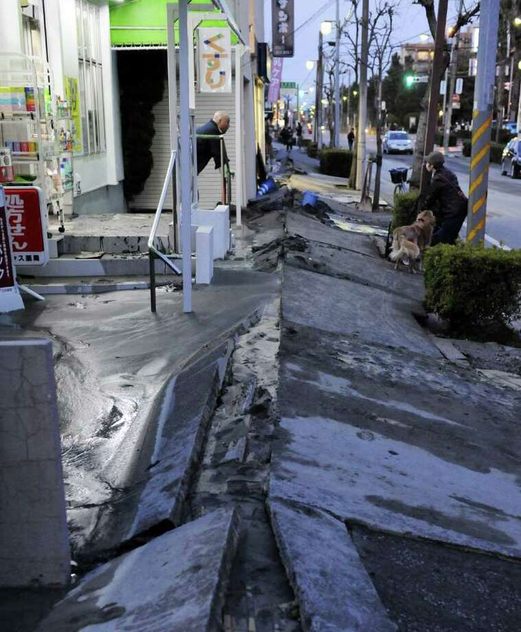 A shop owner chats with a neighbour as the pedestrian road has collapsed in the massive 8.9-magnitude earthquake in Urayasu city, Chiba prefecture on March 11, 2011.  The earthquake shook Japan, unleashing powerful tsunamis that sent ships crashing into the shore and carried cars through the streets of coastal towns.      AFP PHOTO / TOSHIFUMI KITAMURA (Photo credit should read TOSHIFUMI KITAMURA/AFP/Getty Images) Photo: TOSHIFUMI KITAMURA