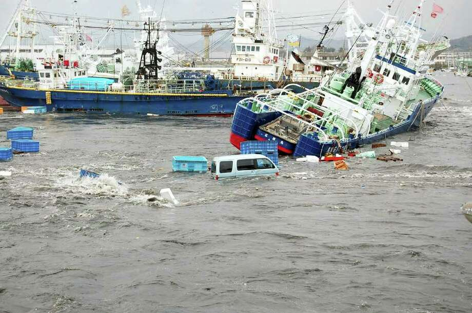 JAPAN OUT Fishing boats and vehicles are carried by a tsunami wave at Onahama port in Iwaki city, in Fukushima prefecture, northern Japan on March 11, 2011.  A massive 8.9-magnitude earthquake shook Japan, unleashing a powerful tsunami that sent ships crashing into the shore and carried cars through the streets of coastal towns.    AFP PHOTO / FUKUSHIMA MINPO via JIJI PRESS (Photo credit should read FUKUSHIMA MINPO/AFP/Getty Images) Photo: FUKUSHIMA MINPO