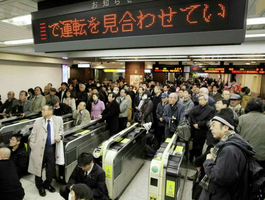 People wait for transport services to resume at the Tokyo station as commuter trains stopped their services in the Tokyo metropolitan area on March 11, 2011.  A massive 8.9-magnitude earthquake shook Japan, unleashing a powerful tsunami that sent ships crashing into the shore and carried cars through the streets of coastal towns.    AFP PHOTO / JIJI PRESS (Photo credit should read STR/AFP/Getty Images) Photo: STR