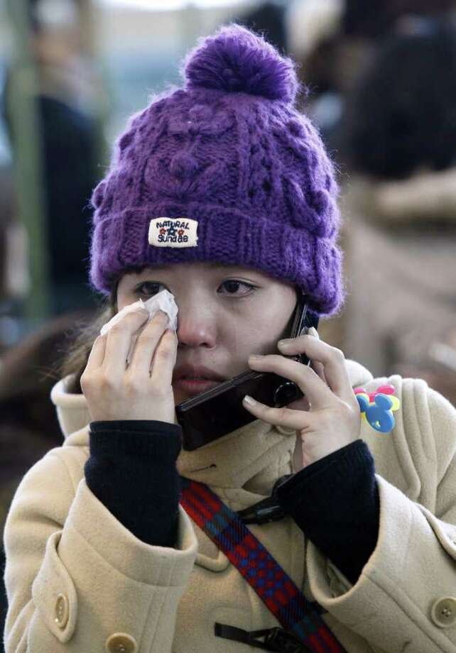 A Japanese traveler wipes tears as she talks over the telephone following a powerful earthquakes that struck off Japan's northeastern coast, at Incheon international airport, west of Seoul on March 11, 2011.  Flights disruptions came hours after a magnitude 8.9 earthquake hit Japan's Pacific Coast, unleashing a tsunami that washed away cars and houses along the coastal areas.    REPUBLIC OF KOREA OUT  NO ARCHIVES  NO INTERNET     AFP PHOTO/YONHAP (Photo credit should read YONHAP/AFP/Getty Images) Photo: YONHAP