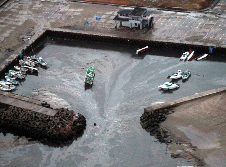 This aerial shot shows boats being carried away at a flooded marina in Hitachinaka city in Ibaraki prefecture on March 11, 2011 after a tsunami hit following an earthquake. A massive 8.9-magnitude earthquake hit northeast Japan, setting a nuclear plant ablaze, unleashing a 10-metre tsunami that tossed ships inland and leaving at least 32 people reported dead.  AFP PHOTO / JIJI PRESS (Photo credit should read JIJI PRESS/AFP/Getty Images) Photo: JIJI PRESS