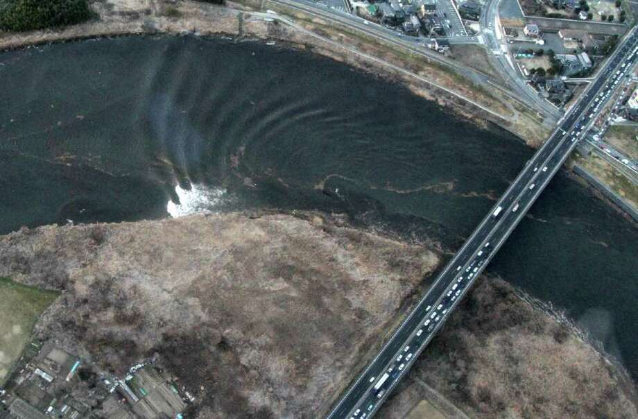 This aerial shot shows the tsunami tidal waves moving upstream (left side) in the Naka river at Hitachinaka city in Ibaraki prefecture on March 11, 2011.  A massive 8.9-magnitude earthquake shook Japan, unleashing a powerful tsunami that sent ships crashing into the shore and carried cars through the streets of coastal towns. AFP PHOTO / JIJI PRESS (Photo credit should read STR/AFP/Getty Images) Photo: STR