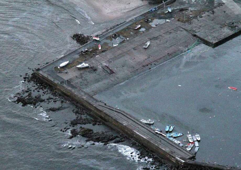 An aerial shot shows washed ashore ships at the port of Hitachinaka city in Ibaraki prefecture on March 11, 2011 after being hit by a tsunami wave following a large earthquake.  A massive 8.8-magnitude earthquake shook Japan, unleashing a powerful tsunami that sent ships crashing into the shore and carried cars through the streets of coastal towns.  AFP PHOTO / JIJI PRESS (Photo credit should read STR/AFP/Getty Images) Photo: STR