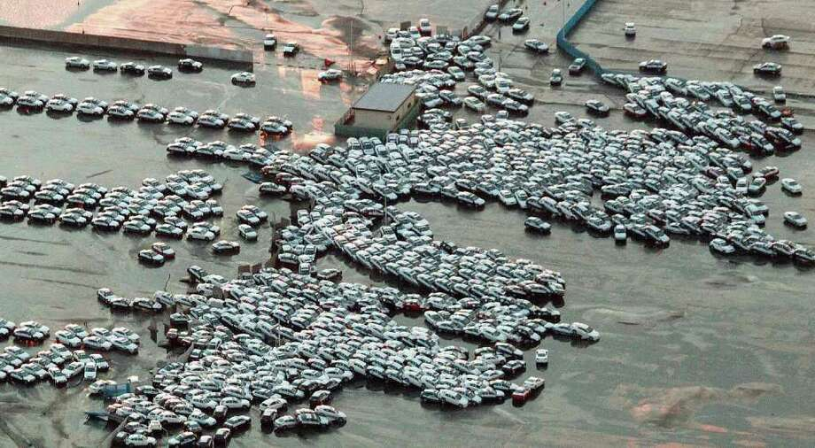 An aerial shot shows vehicles ready for shipping being carried by a tsunami tidal wave at Hitachinaka city in Ibaraki prefecture on March 11, 2011.  A massive 8.8-magnitude earthquake shook Japan, unleashing a powerful tsunami that sent ships crashing into the shore and carried cars through the streets of coastal towns.    AFP PHOTO / JIJI PRESS (Photo credit should read STR/AFP/Getty Images) Photo: STR