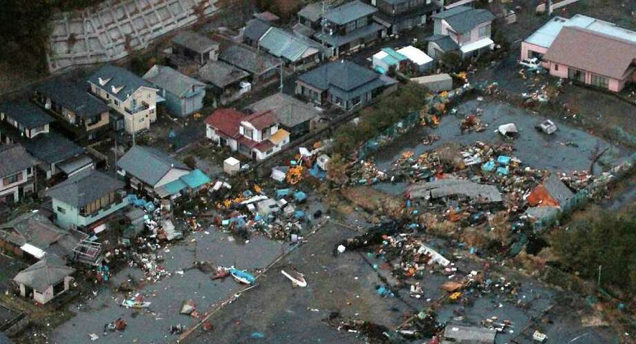 An aerial view shows debris that remained on the ground after a tsunami wave to have hit Hitachinaka city in Ibaraki prefecture on March 11, 2011.  A massive 8.8-magnitude earthquake shook Japan, unleashing a powerful tsunami that sent ships crashing into the shore and carried cars through the streets of coastal towns. AFP PHOTO / JIJI PRESS (Photo credit should read STR/AFP/Getty Images) Photo: STR