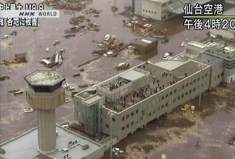 "RESTRICTED TO EDITORIAL USE - MANDATORY CREDIT "" AFP PHOTO / HO / NHK"" - NO MARKETING NO ADVERTISING CAMPAIGNS - DISTRIBUTED AS A SERVICE TO CLIENTS A screen grab taken from news footage by Japanese public broadcaster NHK on March 11, 2011 shows people standing on the roof of the flooded airport and its tower control in Sendai.  A massive 8.9-magnitude earthquake shook Japan, unleashing a powerful tsunami that sent ships crashing into the shore and carried cars through the streets of coastal towns.    JAPAN OUT AFP PHOTO / HO / NHK (Photo credit should read STR/AFP/Getty Images) Photo: STR"