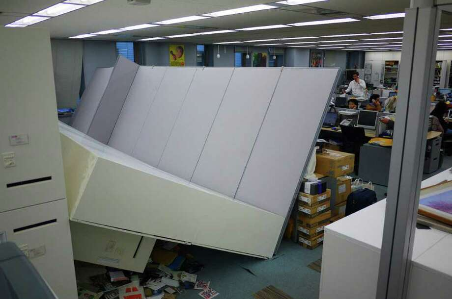 People continue to work in an office after tremors from a massive off-shore earthquake shook the building and knocked over a row of cabinets in Tokyo on March 11, 2011. One of the strongest earthquakes ever recorded hit Japan on March 11, unleashing a 10-metre high tsunami that tossed ships inland and sparked fears that destructive waves could hit across the Pacific Ocean.  MANDATORY CREDIT  AFP PHOTO / HIROKI 'DUKE' KOBAYASHI (Photo credit should read HIROKI 'DUKE' KOBAYASHI/AFP/Getty Images) Photo: HIROKI 'DUKE' KOBAYASHI