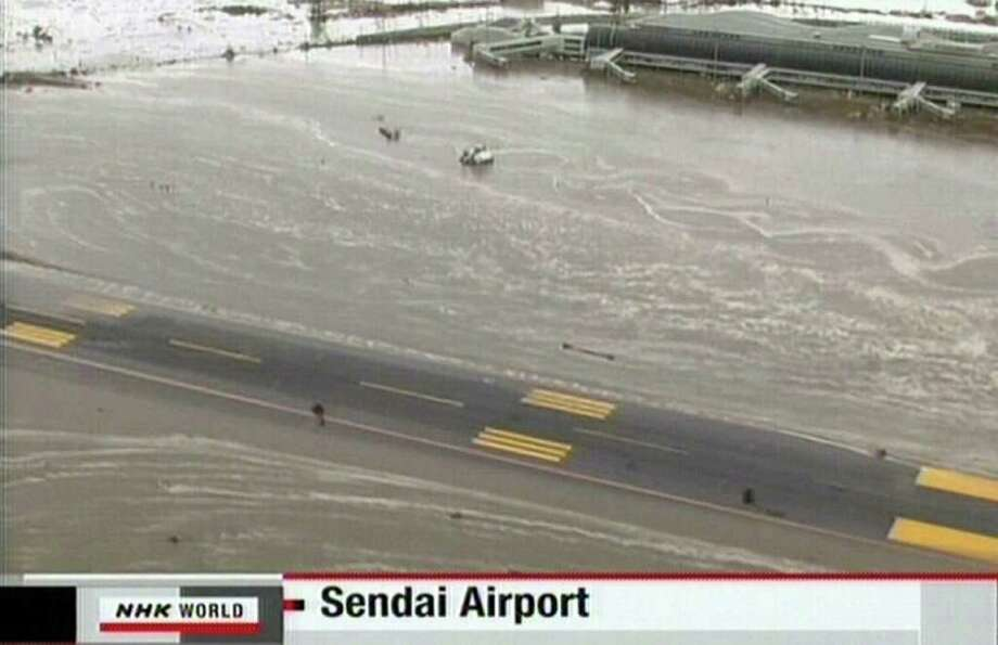 "RESTRICTED TO EDITORIAL USE - MANDATORY CREDIT "" AFP PHOTO / HO / NHK"" - NO MARKETING NO ADVERTISING CAMPAIGNS - DISTRIBUTED AS A SERVICE TO CLIENTS A screen grab taken from news footage by Japanese public broadcaster NHK on March 11, 2011 shows the flooded runway and airport in Sendai.  A massive 8.9-magnitude earthquake shook Japan, unleashing a powerful tsunami that sent ships crashing into the shore and carried cars through the streets of coastal towns.    JAPAN OUT AFP PHOTO / HO / NHK (Photo credit should read STR/AFP/Getty Images) Photo: STR"