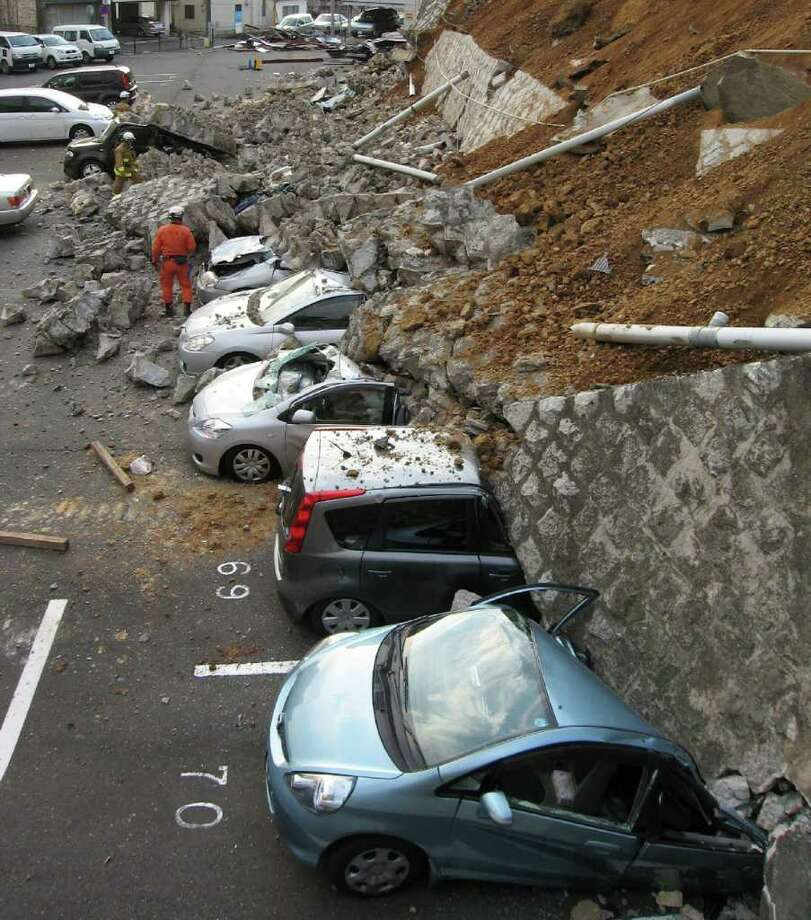 Vehicles are crushed by a collapsed wall at a carpark in Mito city in Ibaraki prefecture on March 11, 2011 after a massive earthquake rocked Japan. massive 8.9-magnitude earthquake hit Japan on March 11, unleashing a monster 10-metre high tsunami that sent ships crashing into the shore and carried cars through the streets of coastal towns. AFP PHOTO / JIJI PRESS (Photo credit should read JIJI PRESS/AFP/Getty Images) Photo: JIJI PRESS