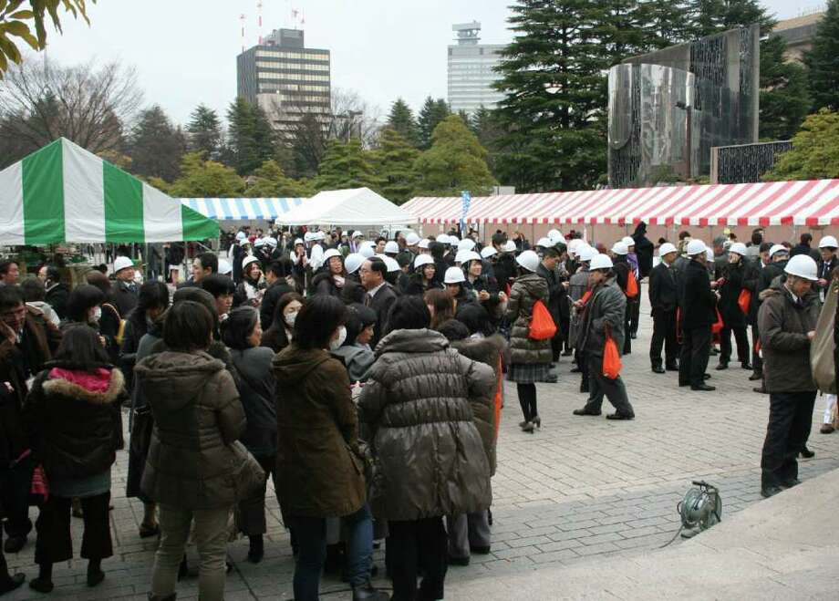 People evacuating gather at a park after a massive earthquake off the coast of Japan at Sendai city in Fukushima prefecture on March 11, 2011.  massive 8.9-magnitude earthquake hit Japan on March 11, unleashing a monster 10-metre high tsunami that sent ships crashing into the shore and carried cars through the streets of coastal towns. AFP PHOTO / JIJI PRESS (Photo credit should read JIJI PRESS/AFP/Getty Images) Photo: JIJI PRESS