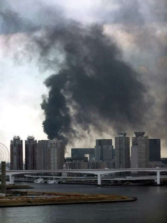 Black smoke raises from a building in Tokyo's waterfront Daiba in Tokyo on March 11, 2011.  A massive 8.8-magnitude earthquake shook Japan, unleashing a powerful tsunami that sent ships crashing into the shore and carried cars through the streets of coastal towns. AFP PHOTO / JIJI PRESS (Photo credit should read STR/AFP/Getty Images) Photo: STR
