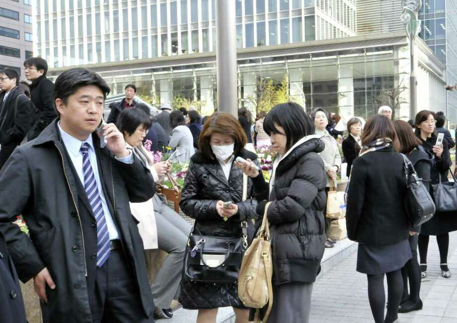 People stand outside a building following a huge 8.8 magnitude quake to hit Japan in Tokyo on March 11, 2011. The huge earthquake shook Japan, unleashing a powerful tsunami that sent ships crashing into the shore and carried cars through the streets of coastal towns.   AFP PHOTO / Yoshikazu TSUNO (Photo credit should read YOSHIKAZU TSUNO/AFP/Getty Images) Photo: YOSHIKAZU TSUNO