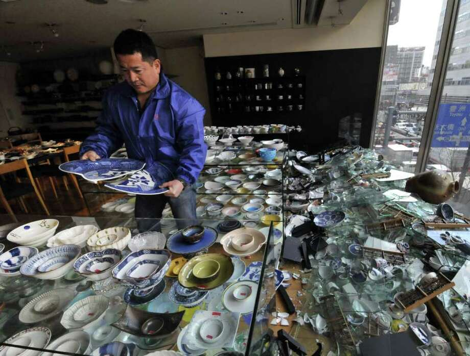 The owner of a ceramic shop checks his damaged wares following the massive 8.9-magnitude earthquake in Tokyo on March 11, 2011. The huge earthquake shook Japan, unleashing a powerful tsunami that sent ships crashing into the shore and carried cars through the streets of coastal towns.   AFP PHOTO / Yoshikazu TSUNO (Photo credit should read YOSHIKAZU TSUNO/AFP/Getty Images) Photo: YOSHIKAZU TSUNO