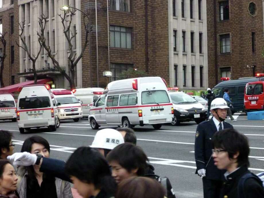 Ambulances gather outside the Kudan Kaikan hall where the ceiling of a school collapsed in the massive 8.9-magnitude earthquake in Tokyo on March 11, 2011. The The huge earthquake shook Japan, unleashing a powerful tsunami that sent ships crashing into the shore and carried cars through the streets of coastal towns. AFP PHOTO / TOSHIFUMI KITAMURA (Photo credit should read TOSHIFUMI KITAMURA/AFP/Getty Images) Photo: TOSHIFUMI KITAMURA