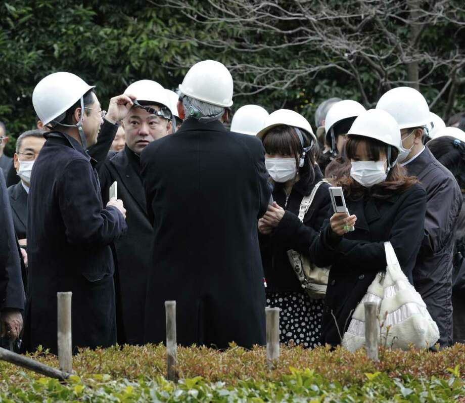People stand outside a building following a huge 8.8 magnitude quake to hit Japan in Tokyo on March 11, 2011. The huge earthquake shook Japan, unleashing a powerful tsunami that sent ships crashing into the shore and carried cars through the streets of coastal towns. AFP PHOTO / Kazuhiro NOGI (Photo credit should read KAZUHIRO NOGI/AFP/Getty Images) Photo: KAZUHIRO NOGI