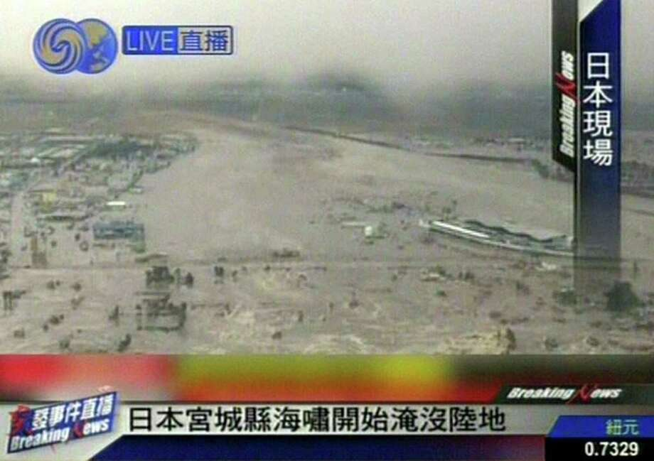 "RESTRICTED TO EDITORIAL USE - MANDATORY CREDIT "" AFP PHOTO / HO / CCTV"" - NO MARKETING NO ADVERTISING CAMPAIGNS - DISTRIBUTED AS A SERVICE TO CLIENTS A screen grab taken from CCTV news footage on March 11, 2011 shows a tsunami hitting the shores of Sendai following an earthquake-triggered tsumani.  A massive 8.8-magnitude earthquake shook Japan, unleashing a powerful tsunami that sent ships crashing into the shore and carried cars through the streets of coastal towns.     JAPAN OUT CHINA OUT  AFP PHOTO / HO / CCTV (Photo credit should read STR/AFP/Getty Images) Photo: STR"