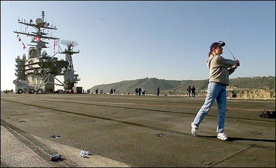 "On the flight deck on the USS Carl Vinson, ""tiger"" Julie Bellman drives golf balls into the Pacific, each one inscribed with the name of a cancer victim. Photo: Gilbert W. Arias/Seattle Post-Intelligencer"