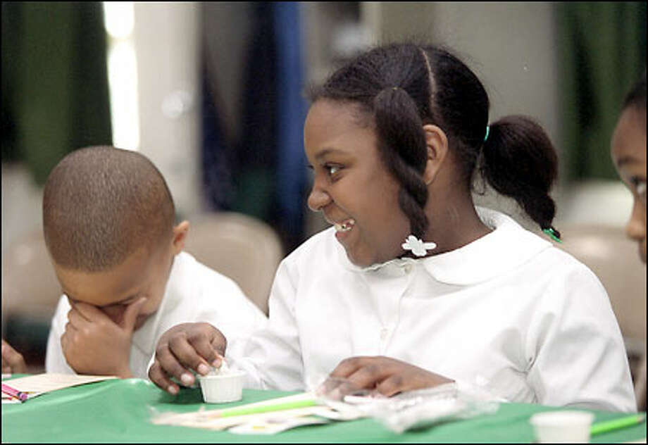 Tyrone Dickens, a fifth-grade student at Washington's Van Ness Elementary School, left, reacts yesterday as fellow fifth-grader Jasmine Parr prepares to eat a yogurt-covered cherry as part of a nationwide taste-testing project. Photo: / Associated Press