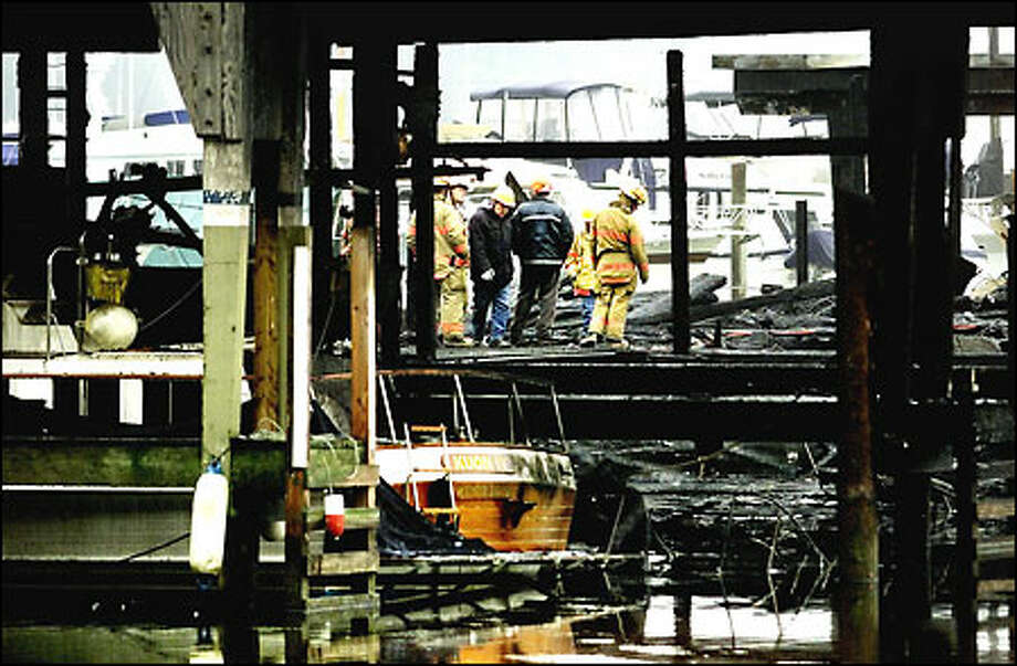 Seattle firefighters yesterday examine the damage to Dock Three at the Seattle Yacht Club caused by a fast-moving fire Tuesday night. Flames of undetermined origin destroyed 13 boats and damaged up to 10 others. Tactical and communications problems hampered firefighters battling the blaze at the historic club on Portage Bay. Photo: Dan DeLong/Seattle Post-Intelligencer