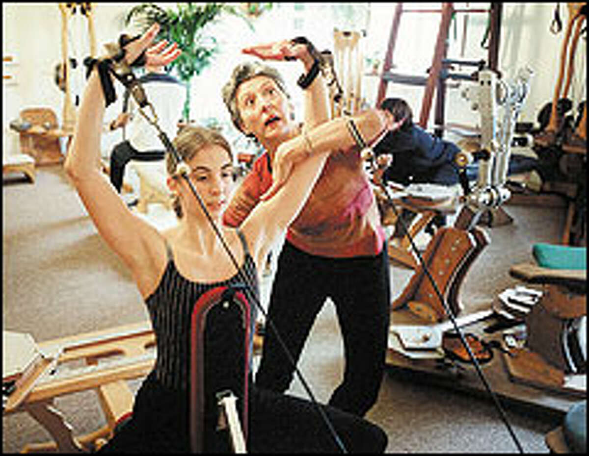 Magali Messac helps Kelly Hartje, a 24-year-old dancer, work out on a Gyrotonic machine.