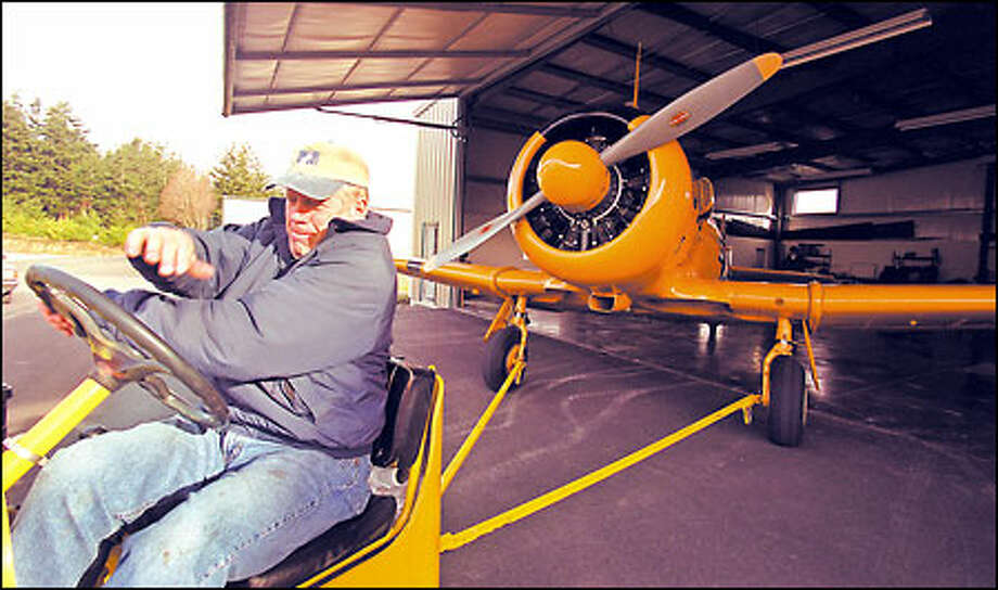 Bill Clapp, who friends say is addicted to flying, backs his 1944 Navy plane into his hanger at the airport on Orcas Island. His first job was a four-year stint as a bush pilot in Alaska. Photo: Phil H. Webber/Seattle Post-Intelligencer