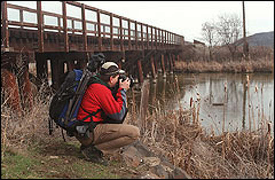 Hiker Alan Bauer zeroes his camera in on some of the native flora along Lower Crab Creek in the stark yet beautiful Columbia Basin. Photo: KAREN SYKES