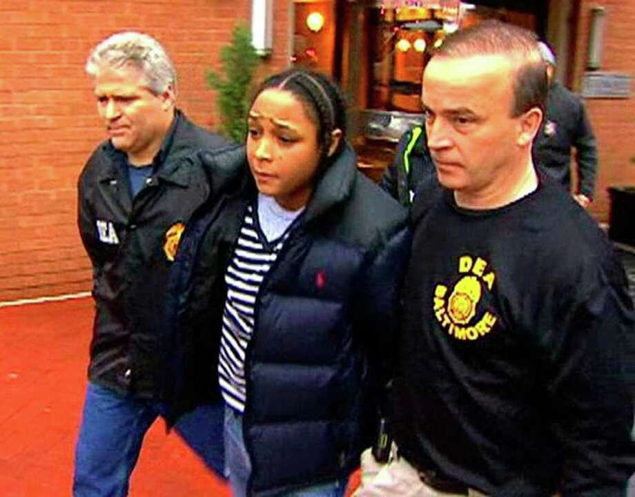 """In this frame grab from video released by WBAL-TV 11, Drug Enforcement Administration agents escort Felicia """"Snoop"""" Pearson, who played a killer of the same name on the hit HBO series """"The Wire,"""" as she was among dozens arrested in an early morning drug raid, Thursday, March 10, 2011, in Baltimore.  (AP Photo/WBAL-TV 11) MANDATORY CREDIT; NO SALES"""
