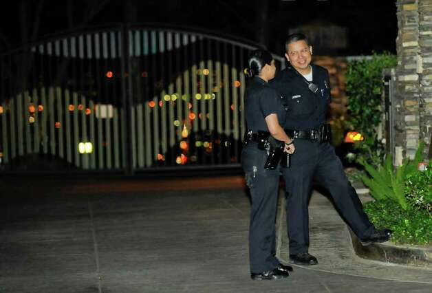 Los Angeles police officers wait outside actor Charlie Sheen's Sherman Oaks home in Los Angeles while other LAPD officer execute a search warrant for weapons, Thursday, March 10, 2011. No weapons were allegedly found. (AP Photo/Gus Ruelas) Photo: Gus Ruelas