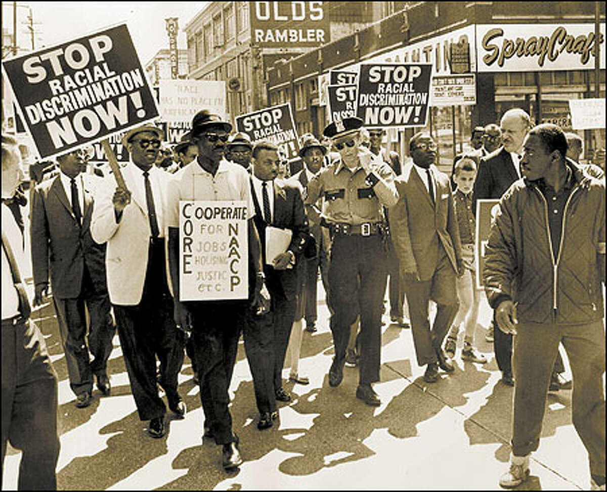 During the summer of 1963, civil rights protestors in Seattle took their fight for racial equality to the streets. Rev. Mance Jackson, center next to Police Sgt. C.R. Connery, and a group of demonstrators that also included whites, march at 13th and Pine on June 15.