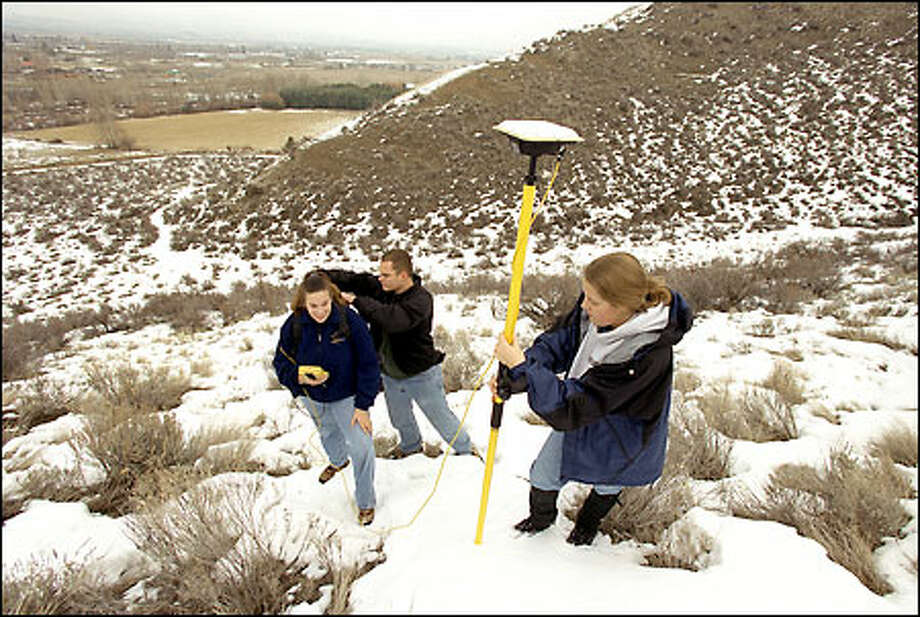 Central Washington University students Carrie Mohler, left, Corey Runge, center, and Syndeny Burch take geodetic measurements near Manastash Ridge using portable GPS equipment. Photo: Gilbert W. Arias/Seattle Post-Intelligencer
