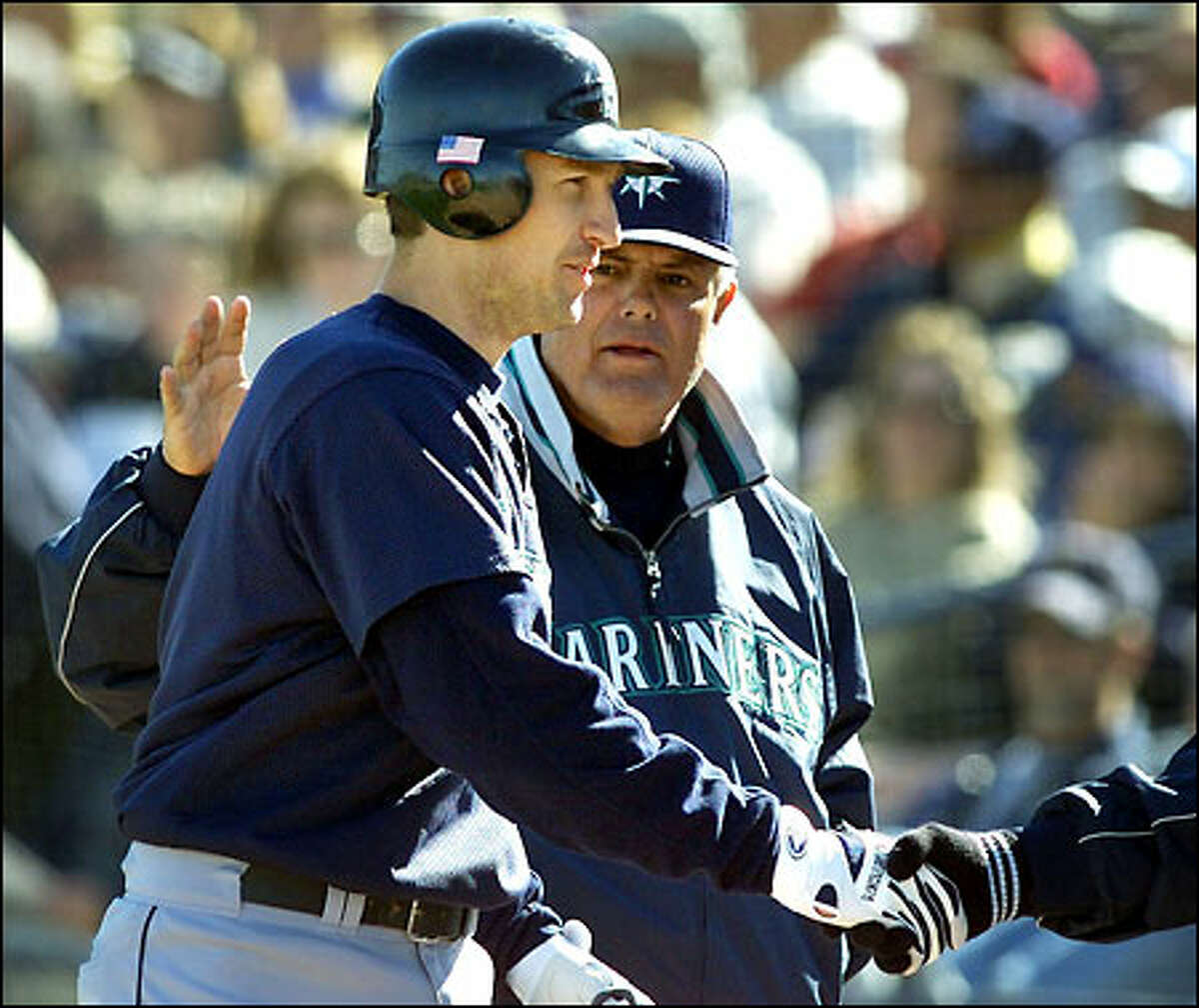 John Olerud receives congratulations from Mariners manager Lou Piniella after scoring during a spring training game against San Diego last week.